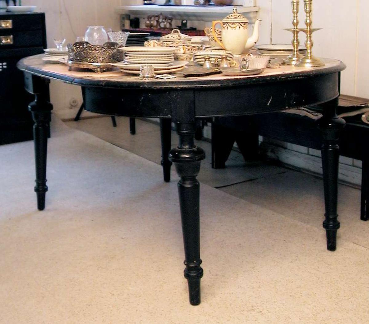 Ovalt spisestuebord med uttrekk og ileggingsplate. Bena er dreide. Bordet er sortmalt. Det er klebet mønstret plast på bordplaten. Fargen under plasten er bondeblå.