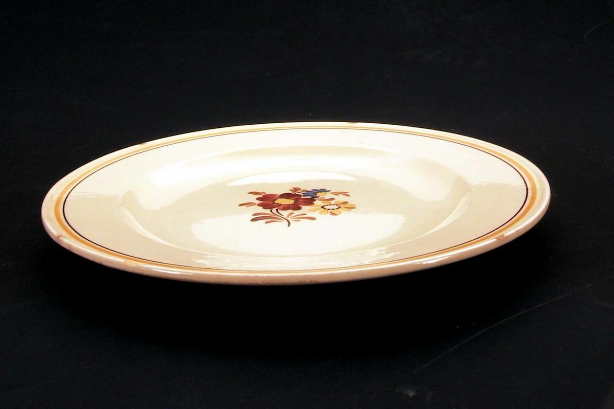 Gul tallerken med blomsterdekor på midten, langs kanten en oker og en brun linje. Det er skår i glasuren langs kanten.
