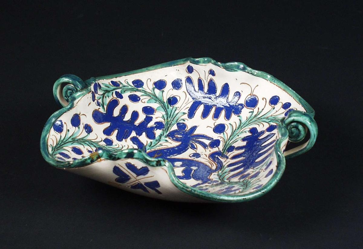 Brukskunst. Fat i keramikk med bølgende, høye kanter og to hanker. Lys glasur med dekor i blått og grønt.