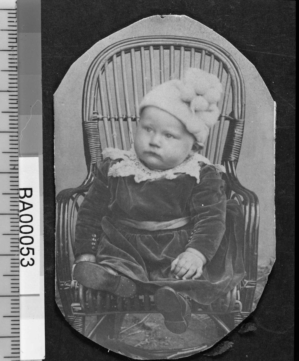 Fotografi av lite barn sittende i kurvstol med lys strikkelue med ponponer festet på siden, mørk kjole med stor hvitt kniplingskrave rundt halsen og sjerf rundt magen, små pynteknapper langs innsiden av mansjettermene. Barnet ser til høyre.