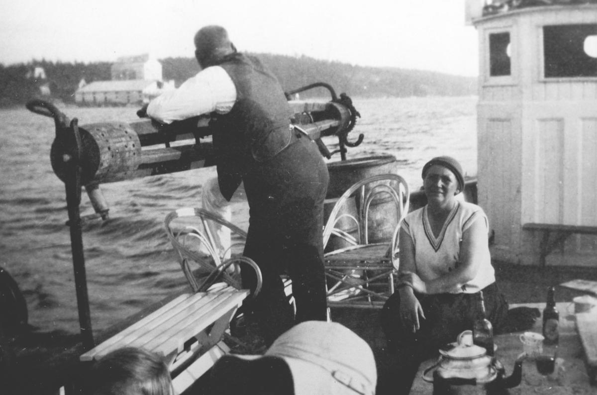 fiskeskøyte, mann i dress og dame med hatt koserseg med kaffe, øl og viv/saft.