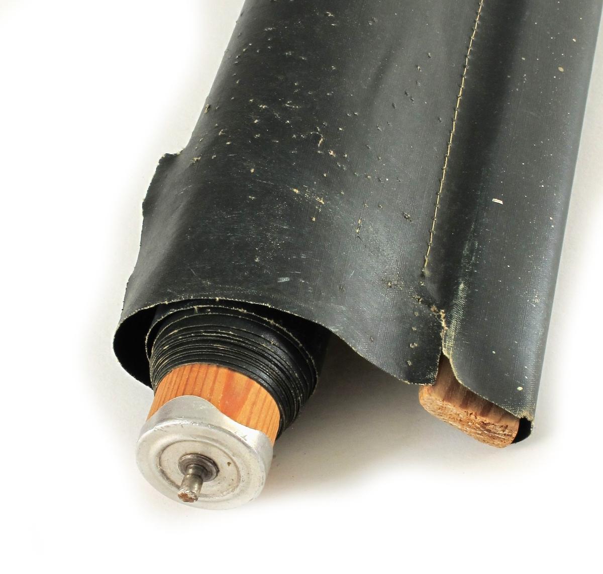 Oljelerret (?) montert på rundstang med fjærer for opptrekk. Snor.  Grønn, mørk, på grensen mot koksgrå.