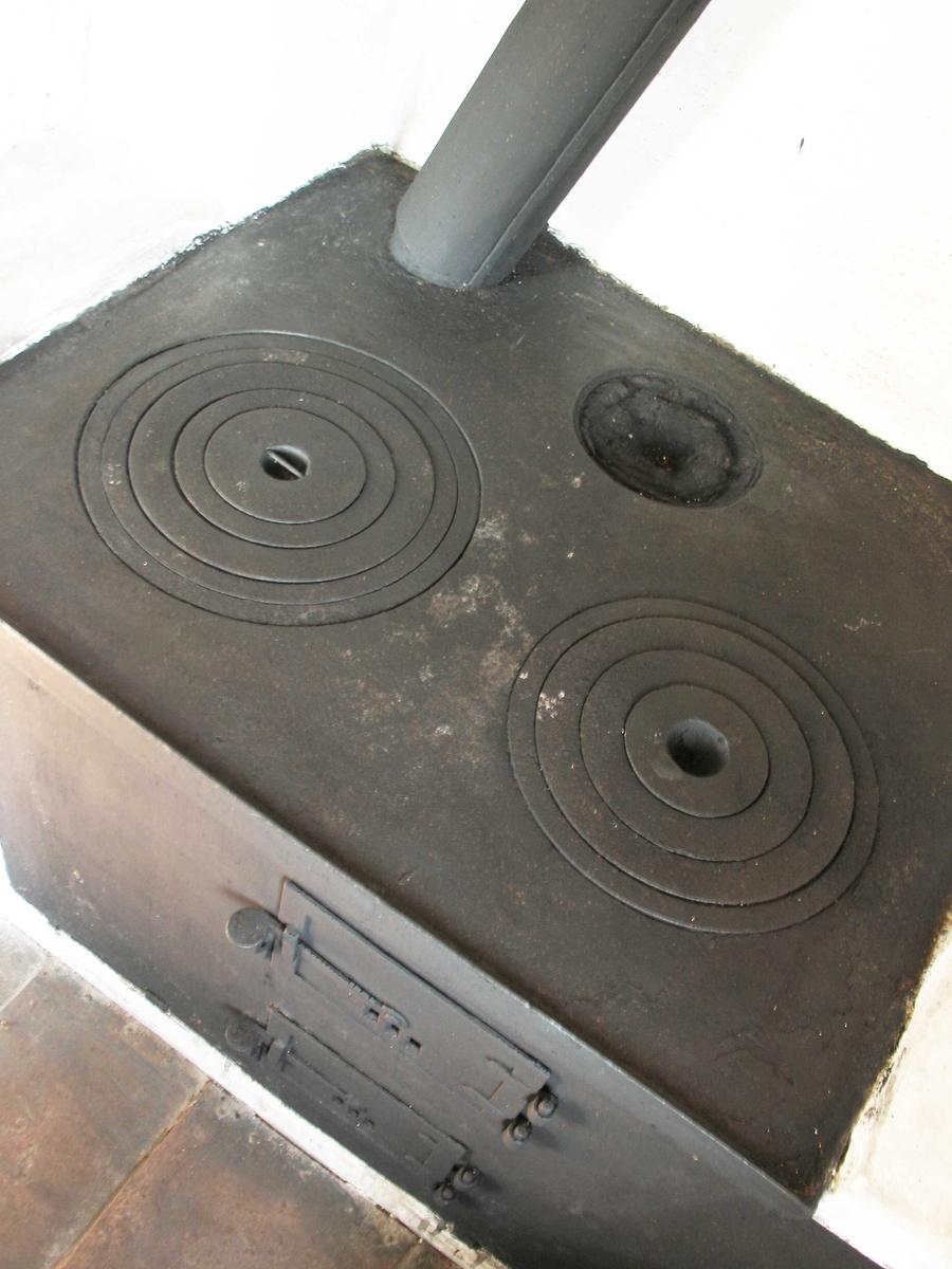 Jernkomfyr, innmurt i grue på kjøkken. Består av:  a) Topplate med to (op rinnelig kanskje tre) utsparinger for gryter av foskjellig størrelse.  b)Frontplate med to dører for fyring og askeuttak. Innvendig askerist av jern.  Det minste bakre kokehull er trolig gjenmurt, mens de to største er komplette. Komfyren er et komplett ildsted med dører, ringer, røykrør og spjeld.