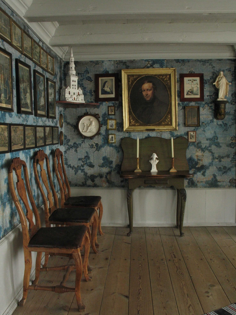 Merdøgaard. Interiør fra Storstua. Stoler, bilder, tapetsert vegg, brystpanel.