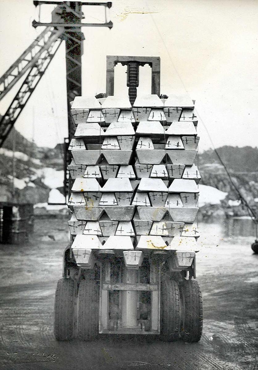 Nitriden. Stabel med støpte aluminiumsbarrer på truck, for transport til lager. De malte symboler er koder tilknyttet produksjonen.