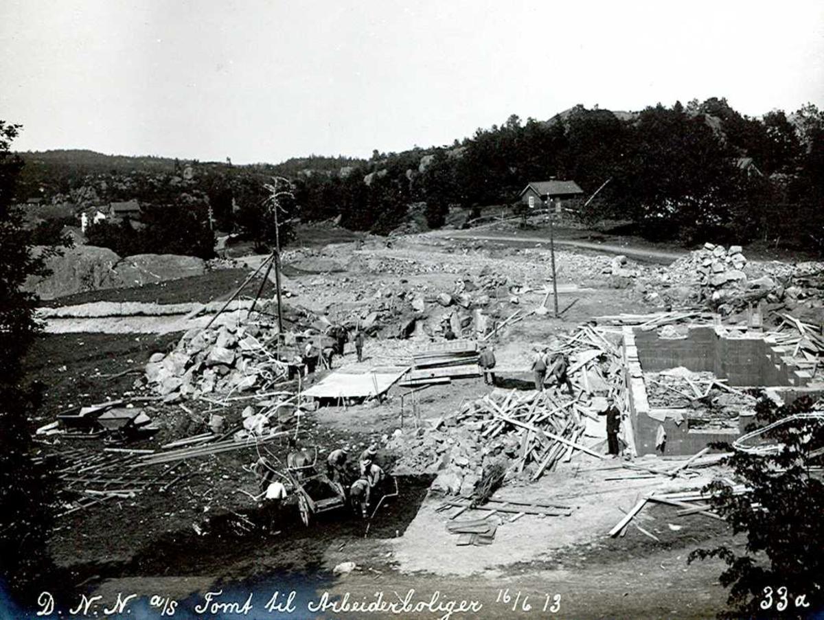 """""""16/06-1913"""" Eydehavn. Utgraving og grunnarbeider for tomter til arbeiderboliger i Nesgaten. Uthuset til høyre tilhørte Mari og Kittel Næs, som bodde like til høyre. Det er fortalt at til et arbeidslag hørt 12-15 mann pluss hest og kjerre."""
