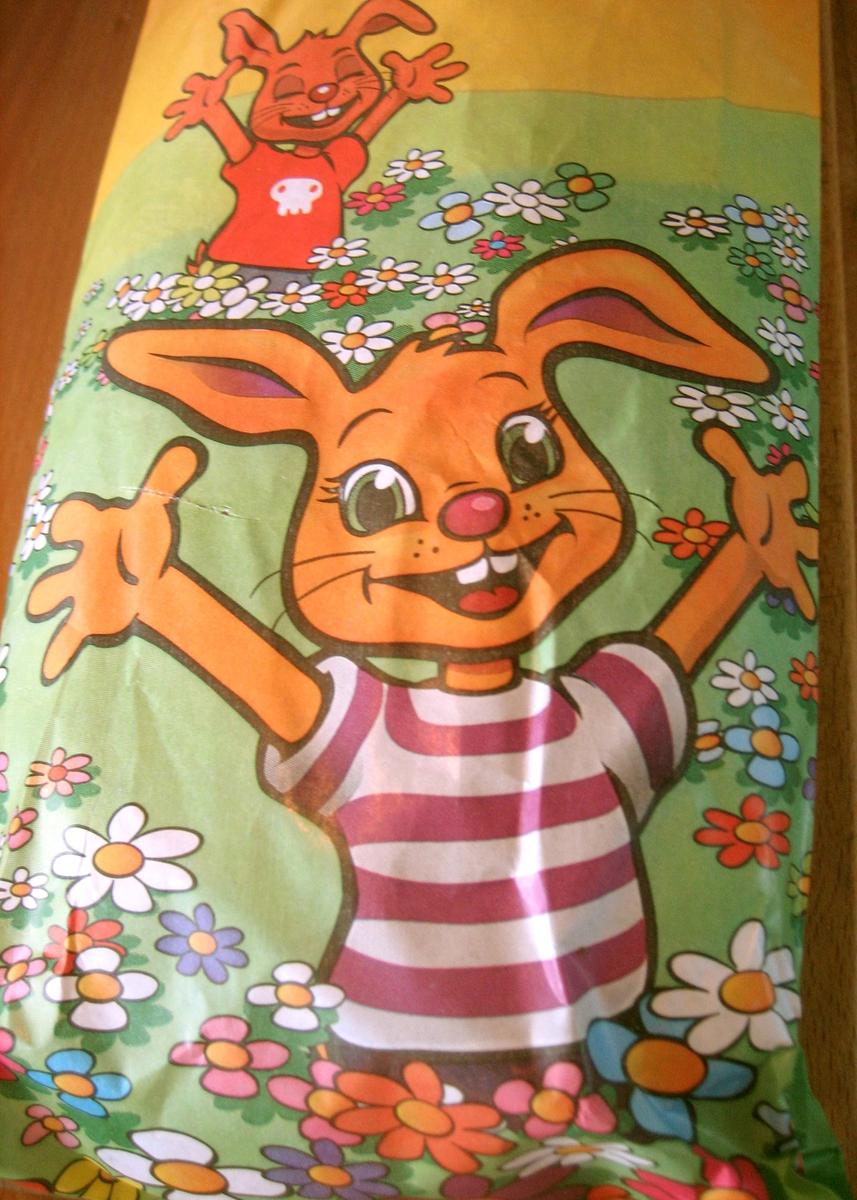 Forsiden: Tegning i farger av to kaniner som står med armene ut i en blomstereng. Baksiden: Tegning i farger av flere smådyr med ballonger som krysser hverandre. Nøkkelhull ikon.