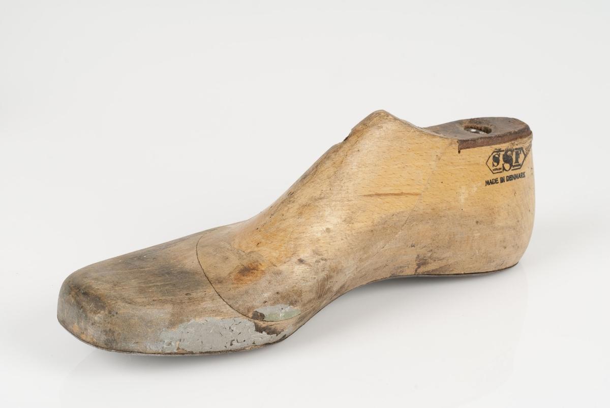 En tremodell i to deler; lest og opplest/overlest (kile). Høyrefot i skostørrelse 43, og 8 cm i vidde. Såle i metall. Lestekam i skinn.