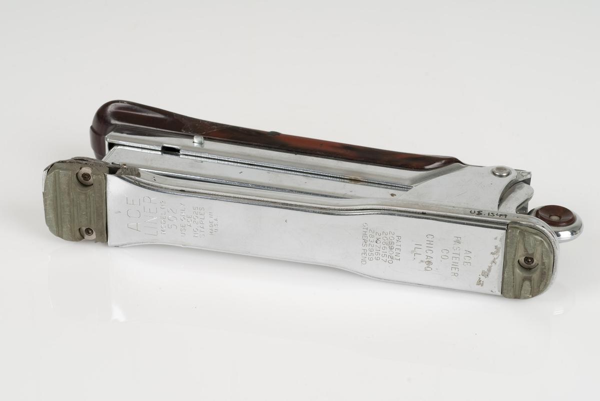 Stiftemaskin av metall og plast med innskrift på topp og bunn.