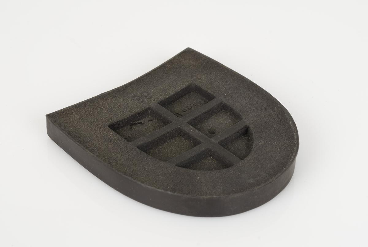 En hælflikk av plast. Fargen på hælflikken er mørk brun. Avtrykksmønster på hælflikken. 8 hull på hælflikken.