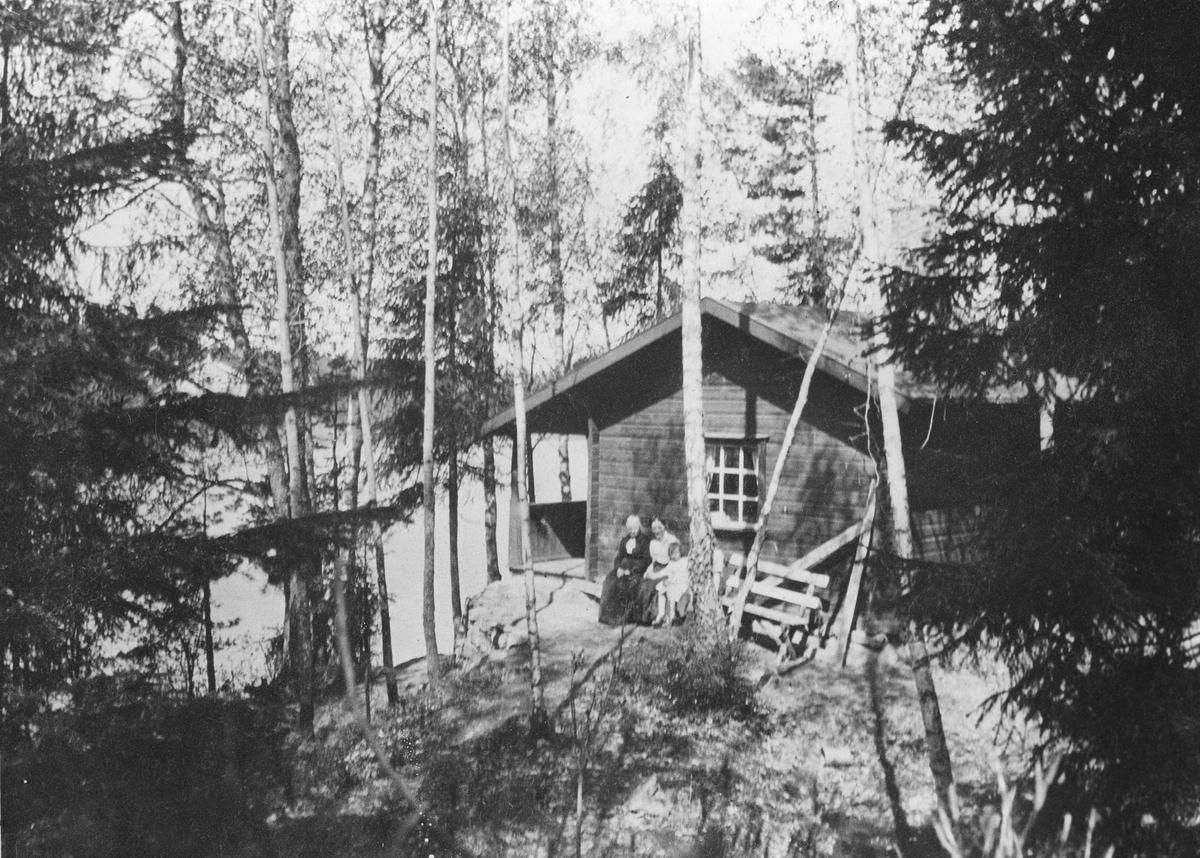Tre personer foran Kjærnstua, Kullebunn