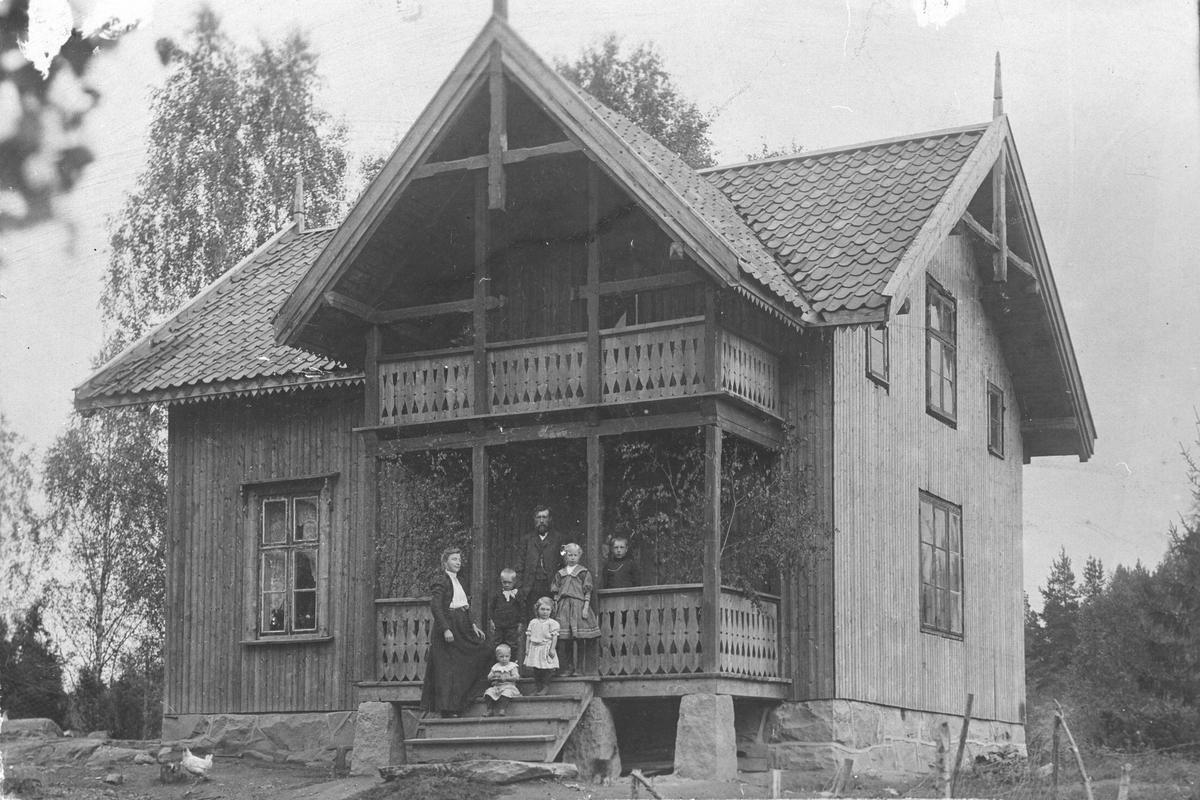 Ektepar med fem barn, stående på veranda i sveitser-hus.