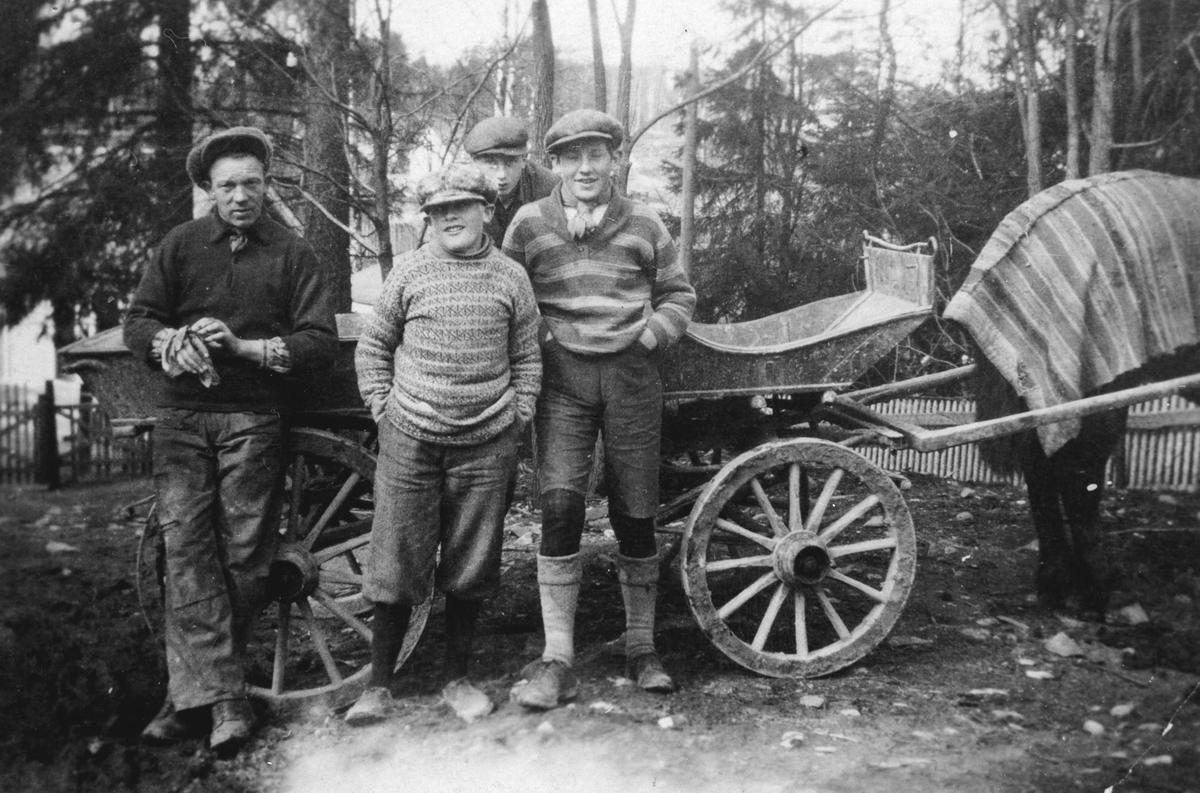 Fire personer foran en kjerre.