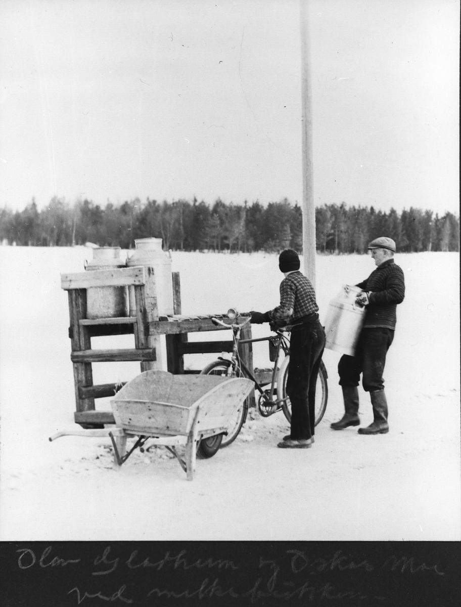 Olav Gladheim og Oskar Moe ved melkebukken, en sykler og en leverer melkespann med trillebår