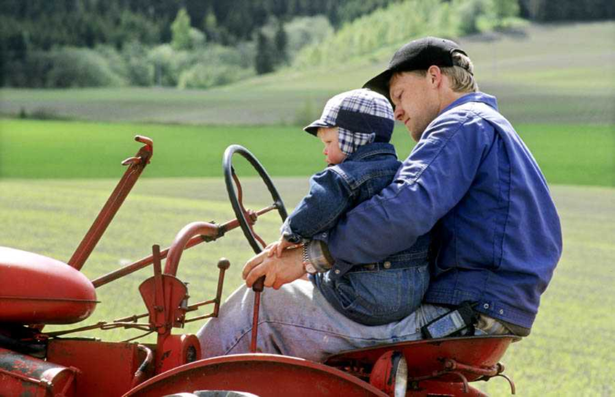 """Dokumentasjon av drenering i forbindelse med åpning av ny utstilling: """"Jordbrukets utvikling på Romerike"""" på Gamle Hvam. Mann og gutt sitter på traktor"""
