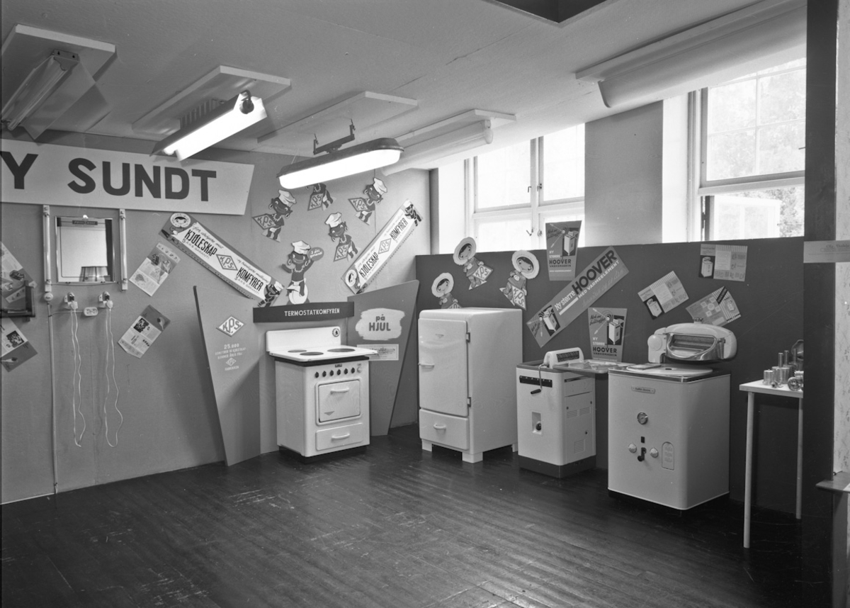 Fra bygdeutstillingen i 1955. PAY SUNDTs forretning: PhiliShave barbermaskin. Ovn (termostatkomfyr) og kjøleskap av merket KPS (K Pettersens sønner A/S, Sarpsborg). Vaskemaskiner av merkene HOOVER og ENGLISH ELECTRIC.