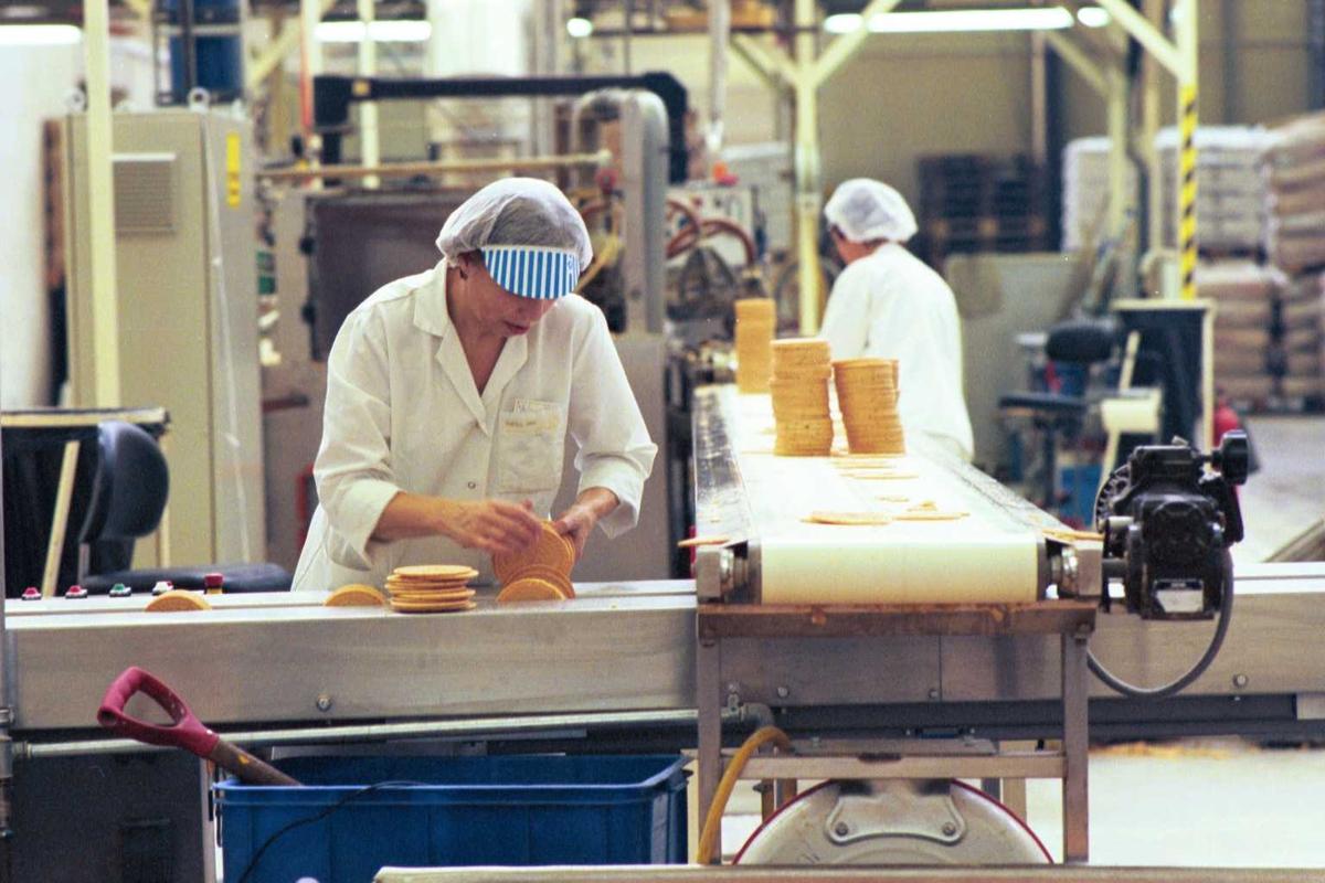Startkjeks, maskiner, arbeidere, kvinner, arbeidstøy, arbeidsmiljø, fabrikkmiljø. Pakkemaskinen mates med kjeks.