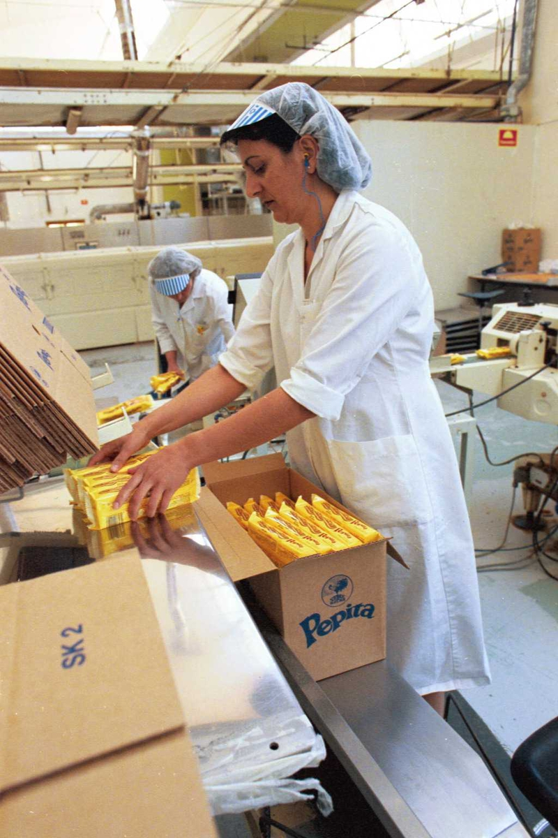 Pepitakjeks legges i kartong, emballasje, arbeidere, kvinner, arbeidstøy, arbeidsmiljø, fabrikkmiljø, maskiner