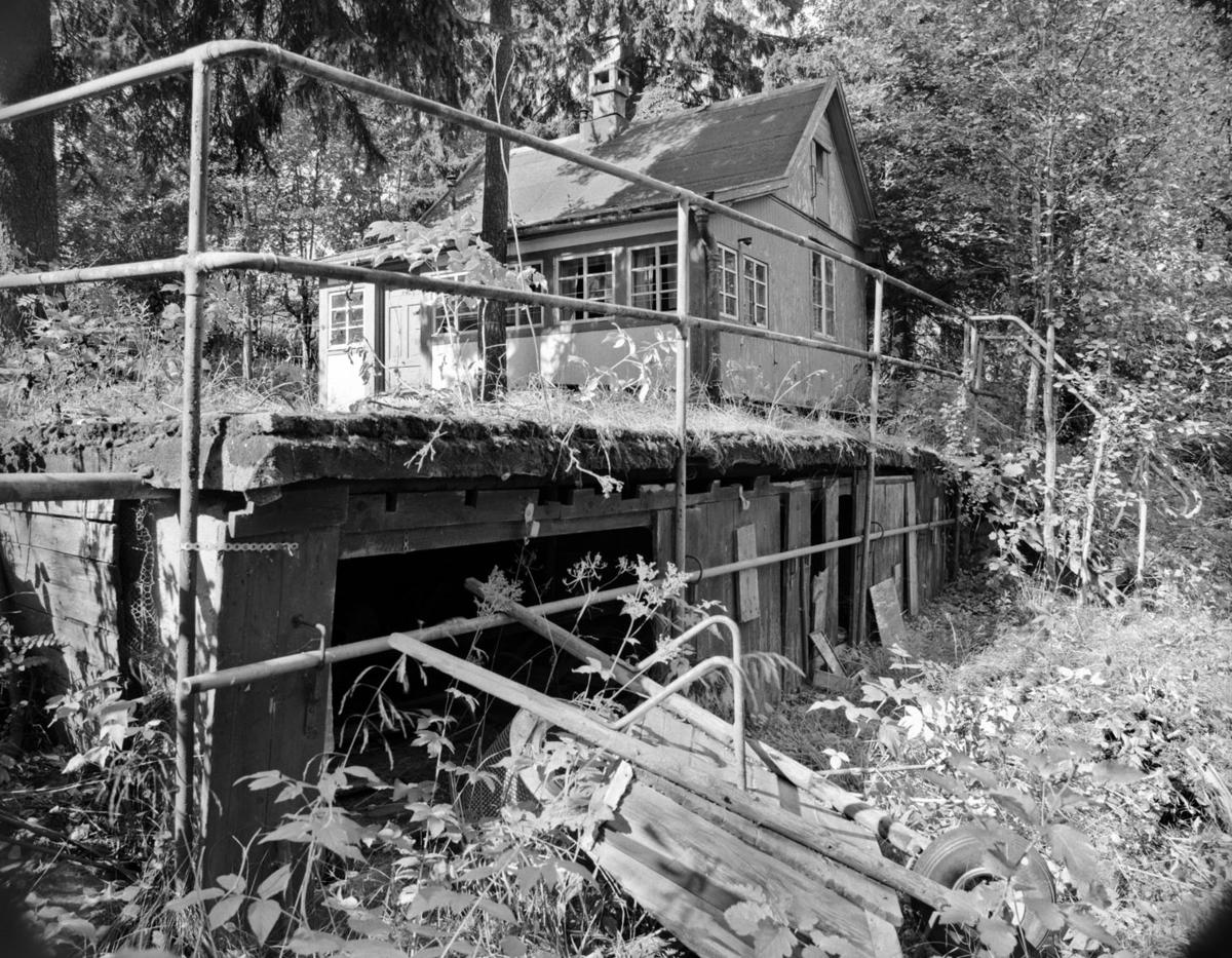 Eksteriør: Hytte står ovenpå noe som ligner en påbygd underetasje med terasse og hytte ovenpå underetasjen. Trillebår i forgrunn.