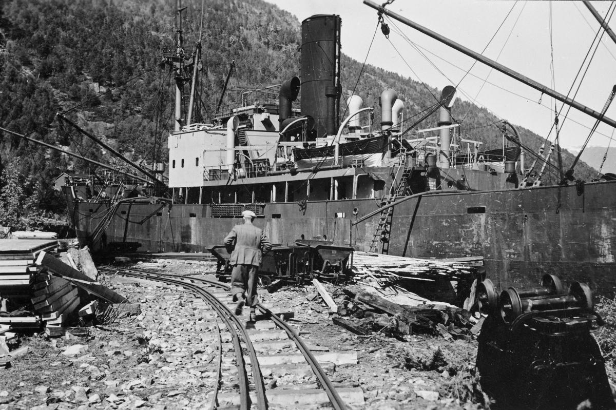Ved Krogshavn, dypvannskaia utenfor Sunndalsøra. Sporet på  Aurabanen var revet opp dit før krigen brøt ut, men tyskere gjenoppbygde sporet med 900 mm sporvidde.  Sporene vi ser må være fra provisorisk, midlertidig  trallebane.   Skipet er det tyske frakteskipet MALAGA.