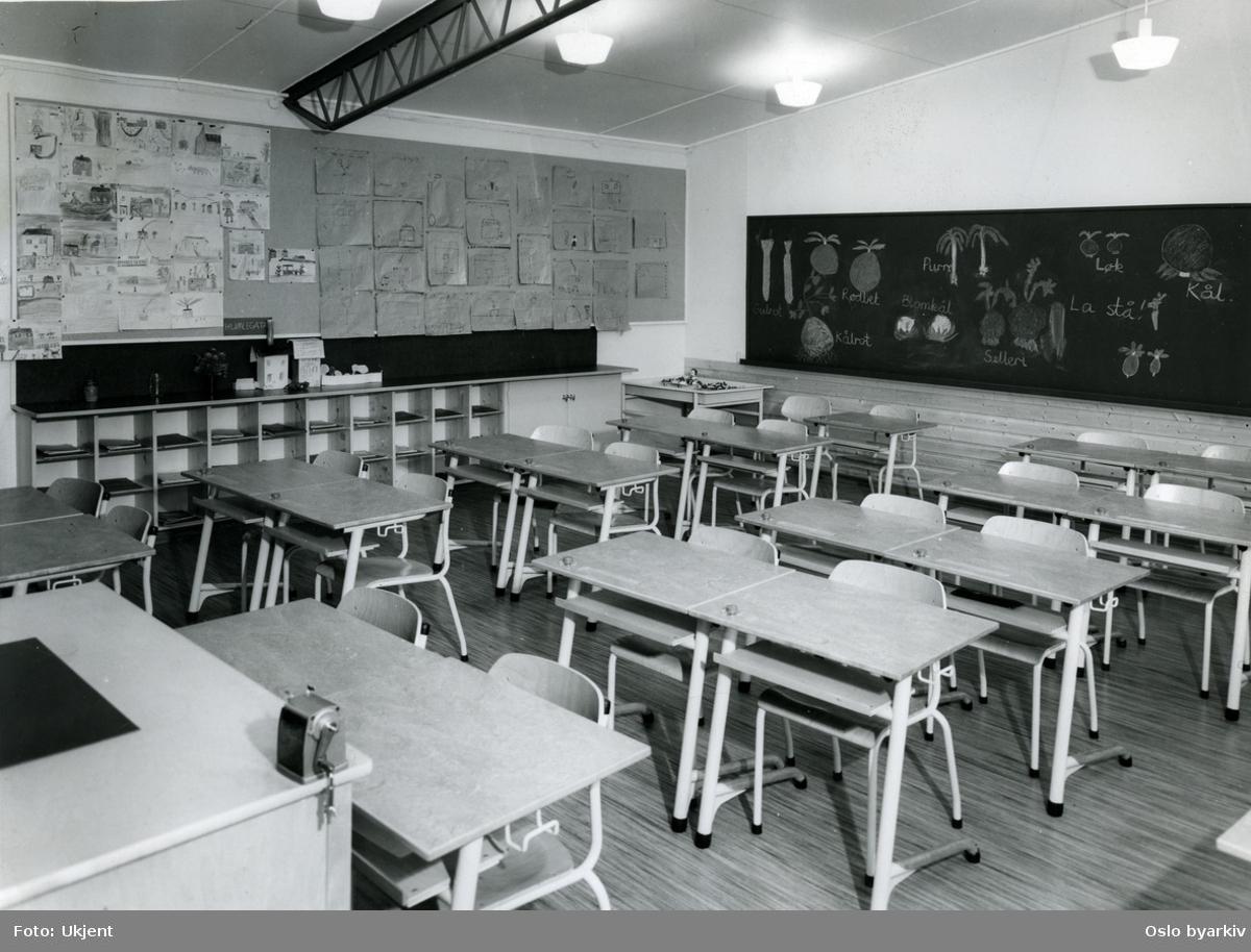 Klasseværelse på Veitvet skole. Barnetegninger på tavle og vegg. Elevarbeider. Veggreol. Pulter (to og to).