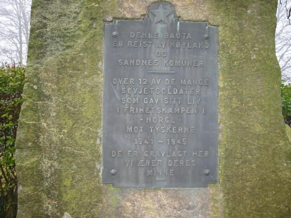 Innegjerdet med kjetting 6x6 m. Med hekk rundt. Statuen i granitt h 180 b 1,0 d 0,6