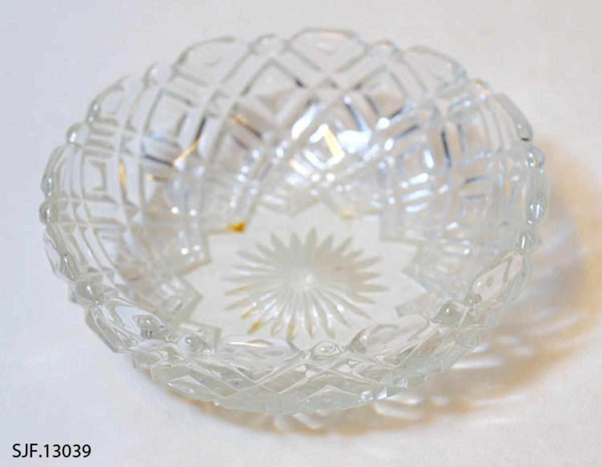 Rund skål i pressglass. Stjernemotiv i bunnen. Kanten er tagget. Et mønster bestående av firkanter på siden.