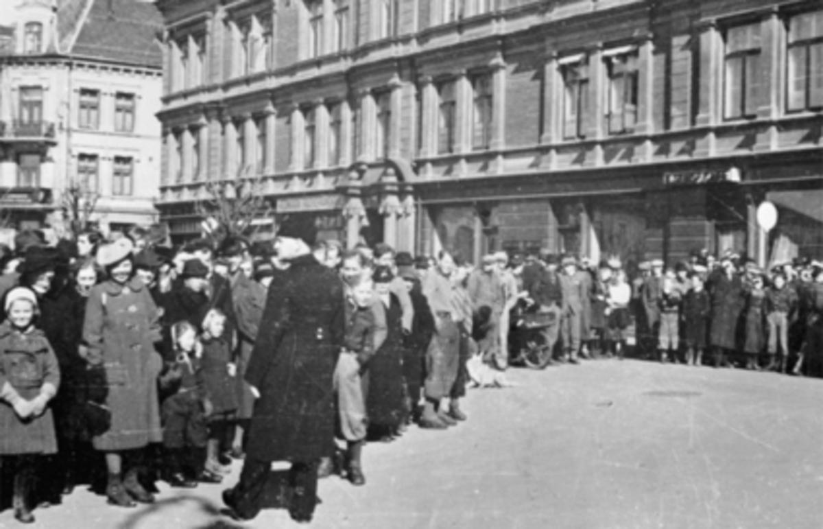 Folkesamling, jernbaneplassen, kongefamilien kommer 09. 04. 1940. Hjørdis Nyang til v. m/kåpe og hatt som smiler.