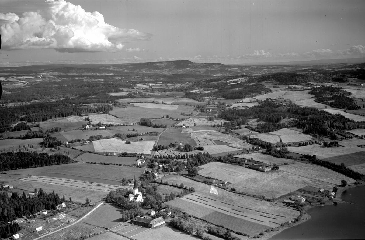 Flyfoto av Ringsaker kirke og landskapet rundt. Høsbjøråsen i bakgrunnen.