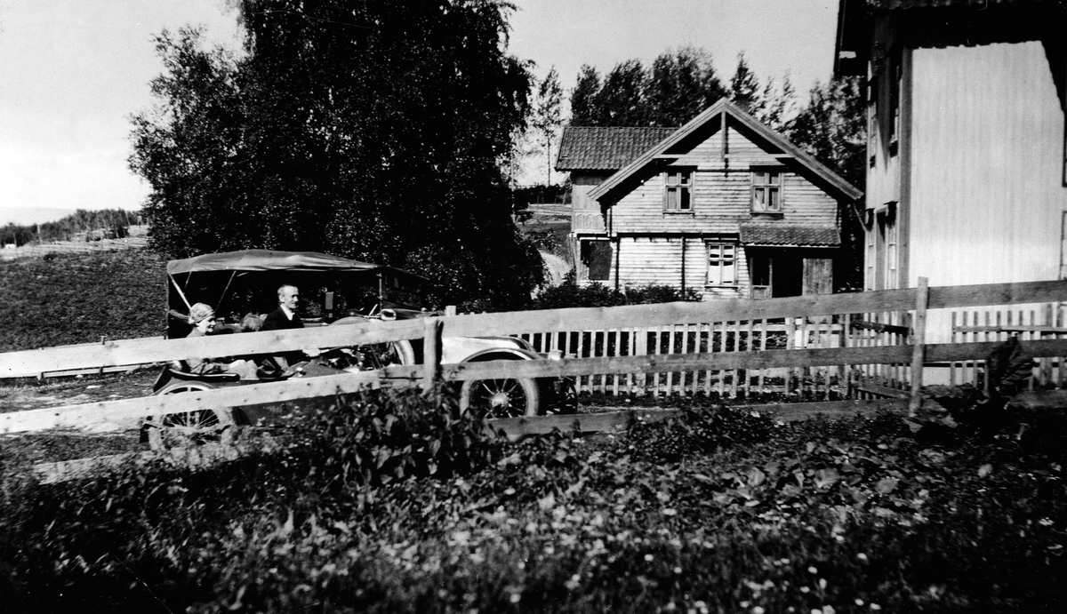 """EKSTERIØR: GARDSBRUK, JØNSRUD, TANGEN, OSLOBIL PÅ BESØK, I BILEN: JULIE OPTJERNSBERGET OG JØRGEN RASEN Jørgen Rasen og Julie Opptjernsberget kommer kjørende på motorsykkel opp mot hovedbygningen. De passerer gammelford`n som står parkert. Bildet er fra 1928. Eier av bilen er ukjent.  Flere opplysninger se boka """"Handelssteder i Stange"""" skrevet av Jan Arne Berg, utgitt av Stange Historielag 2012"""