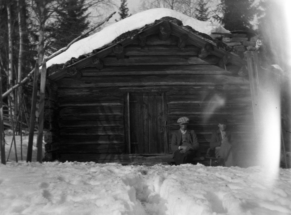 Eksteriør, skog, ski, vinter. To ukjente menn sitter ved en koie. Den ene røyker pipe.