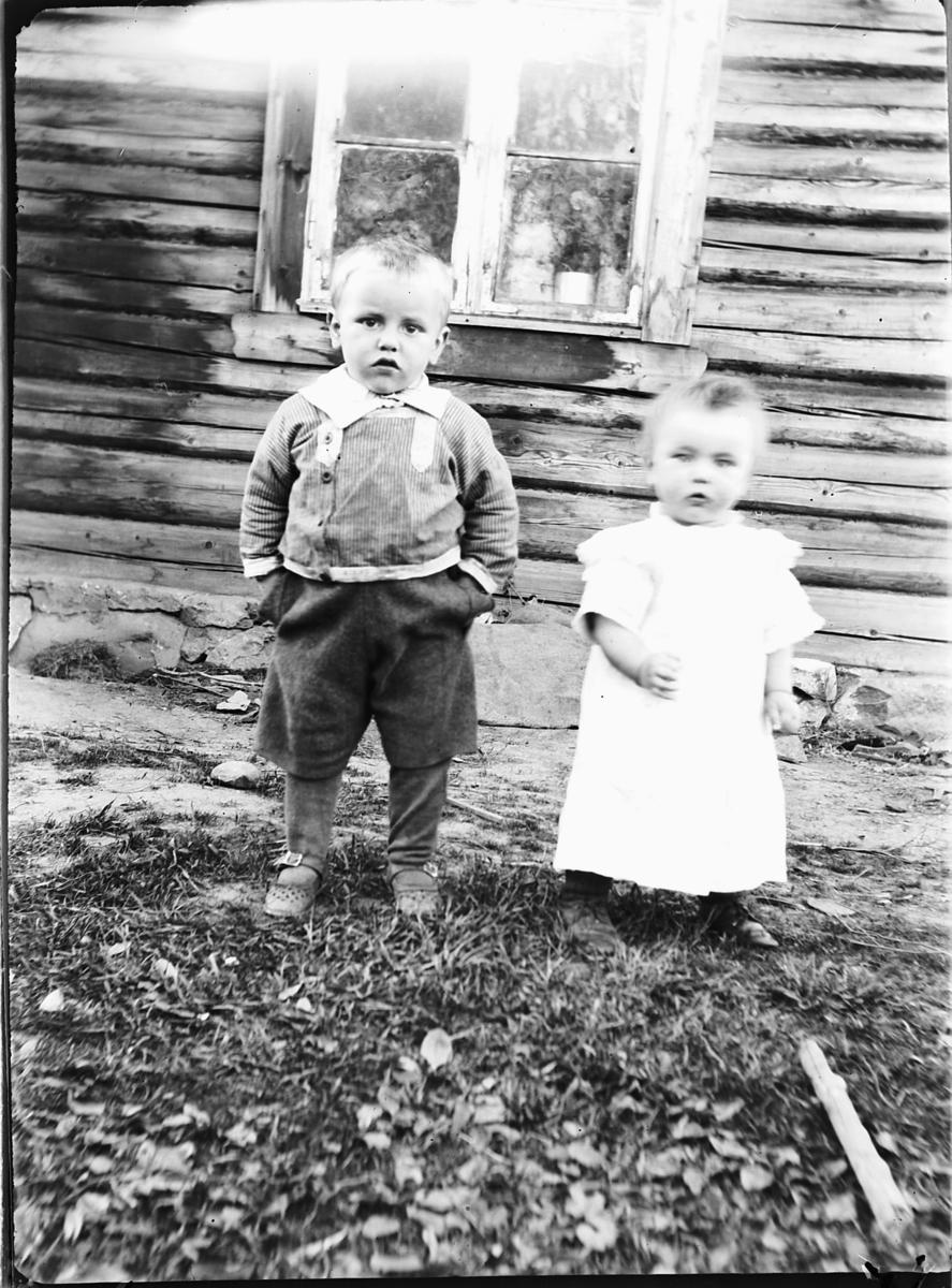 En liten gutt og jente utenfor et hus.