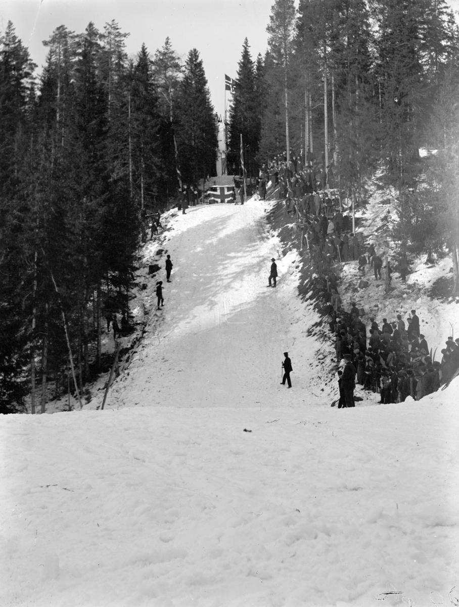Hopprenn i Hamarbakken. Publikum ser på en skihopper i svevet i Hamarbakken.