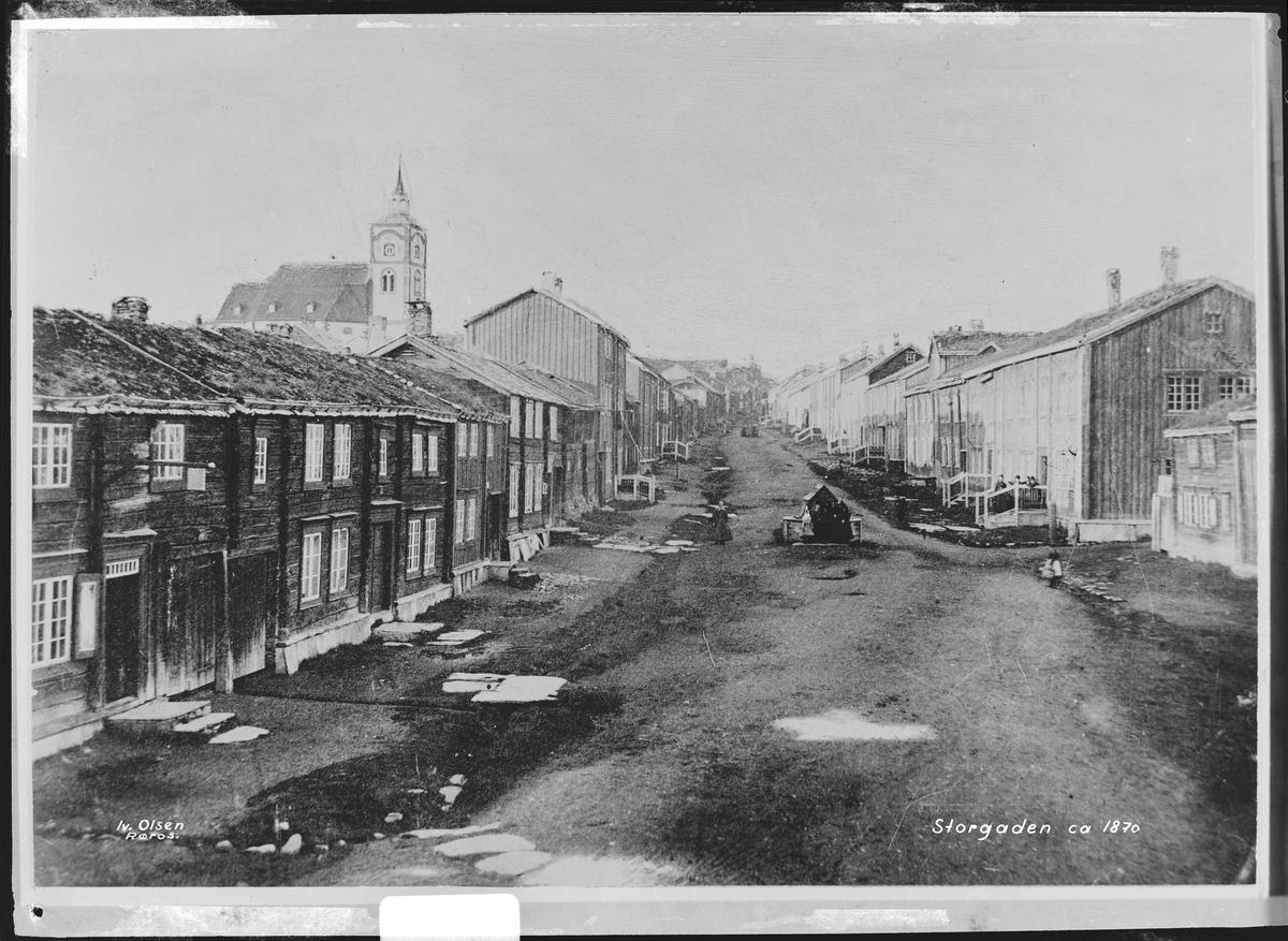 Bergmannsgata på Røros ca 1870. Vannpost midt i bildet og bebyggelse på begge sider av gata fra sørenden og oppover.