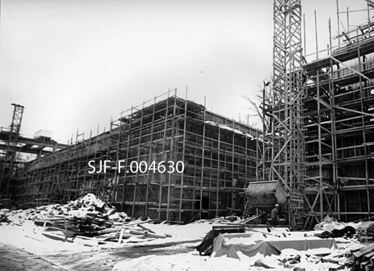 Fra bygginga av nytt renseri og hoggeri med tilhørende kranbane ved Union Bruk i Skien vinteren 1965-66.  Dette er et eksteriørbilde, tatt mot to bygninger som var omgitt av treforskalinger og trestillaser.  Den største av dem (til venstre) er den som skulle huse fabrikkens nye renseri og flishoggeri.  Til venstre for den igjen skimter vi noe av kranbanen, som skulle brukes til å hente tømmer til anlegget.  Den besto av to parallelle søylerekker med horisontale baner på toppen, alt utført i armert betong.  Mellom disse banene ble det montert ei kraftig stålbru med ei kran som kunne beveges sidevegs mellom fløtingsvassdraget og vegen dette fotografiet er tatt fra, hvor det ble levert tømmer på lastebillass.  Mellom disse ytterpunktene, ved en av fabrikkhallens gavlvegger, lå nedleggsbordet, som var inntakspunktet for tømmerråstoff til renseriet og hoggeriet.  Da dette fotografiet ble tatt var byggeplassen dekt av et tynt snølag.  Mellom vegen i forgrunnen og bygningene lå det både masse (jord og stein) og en del materialer, antakelig fra forskalingsarbeidet.