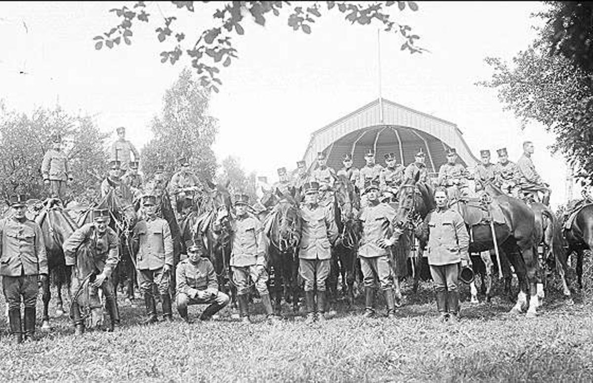 Avdelning under rast. Soldaterna är iklädda uniform m/1910 och mössa m/ä. Även furiren längst fram till höger har uniform m/1910. I bakgrunden till höger syns musikpaviljongen och till vänster del av syrénbersån i vilken K 3:s dansbana låg.