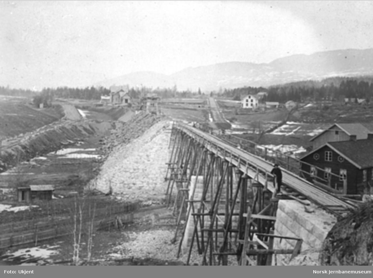 Bru over Moelva sett sørfra med stasjonsanlegget i bakgrunnen : brua har spor, men foreløpig på pæler
