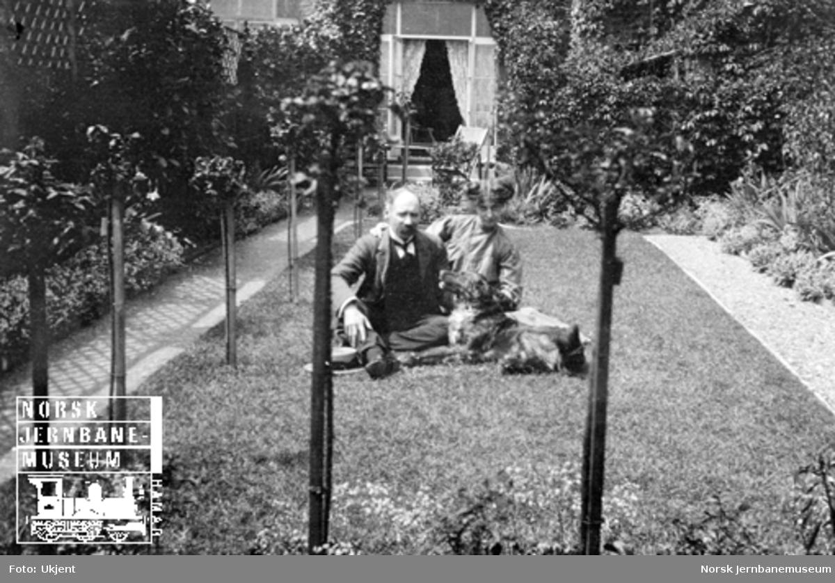 Familiebilder : et par med hund på gressplenen foran huset