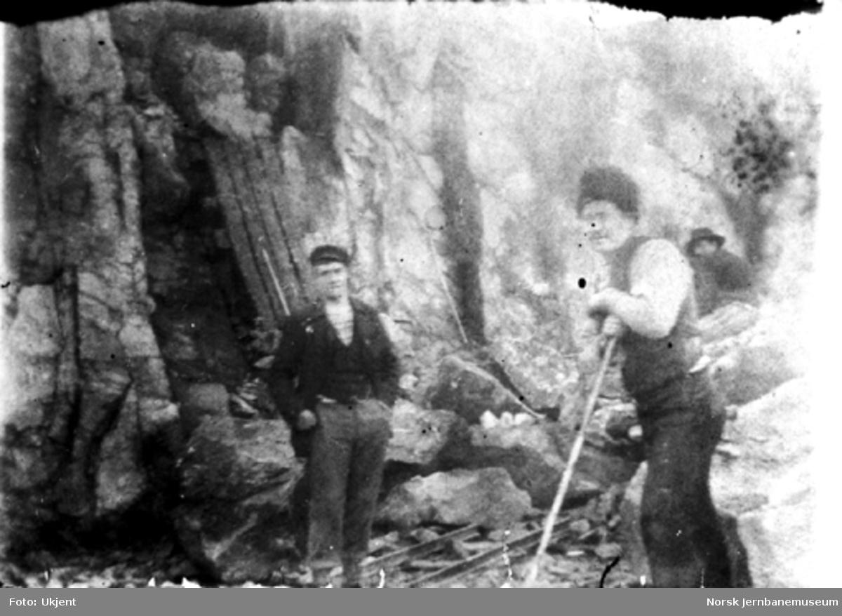 To anleggsarbeidere i en skjæring på ukjent bane