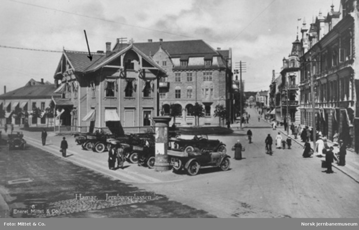 Hamar : Jernbaneplassen med den gamle stasjonsbygningen og parkerte biler