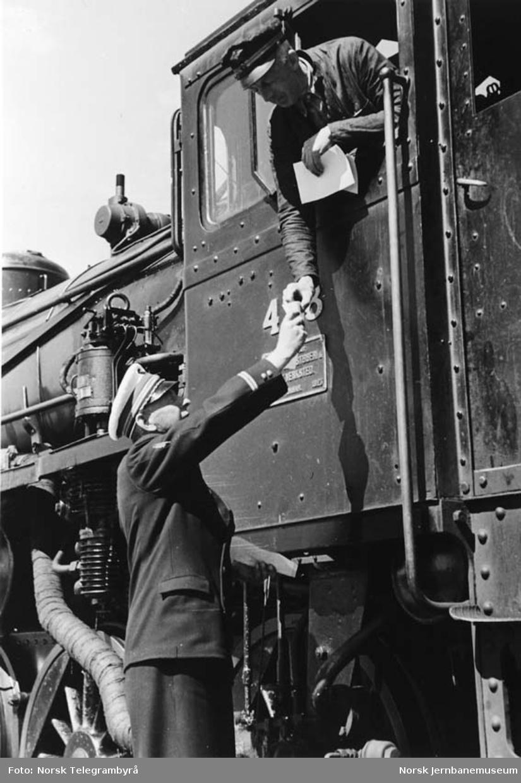 Stasjonsmesteren overleverer kjøreordre til lokomotivfører Kristian Alfr. Andersen