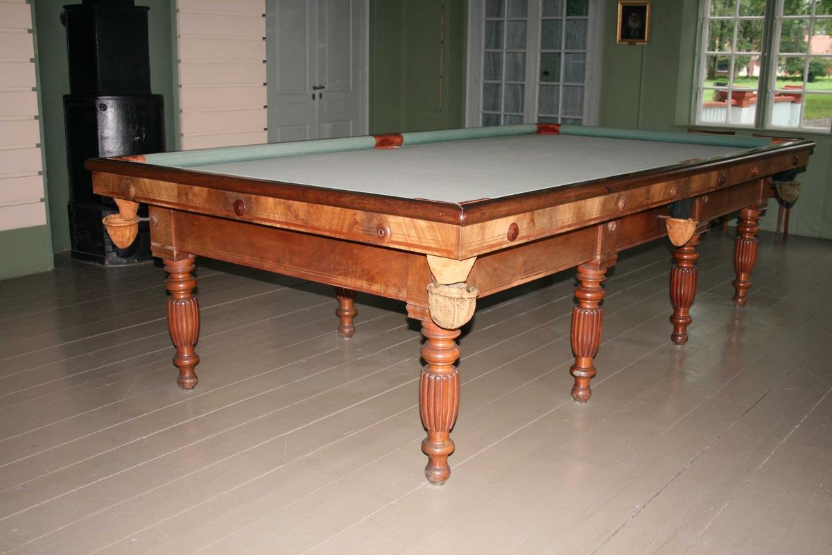 Stort rektangulært bord. Bordplate av tre, trukket med grønn filt. 6 hull m/skinnposer til kulene. 8 dreide bein - balusterbein. Sein-empire, biedermeier. Det er ikke et snooker-bord (snooker er en litt nyere form for billiard).