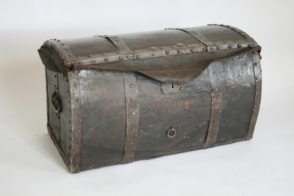 Reisekiste fra ca. 1800. Avrundet, jernbeslått, skinnflik over låsen.