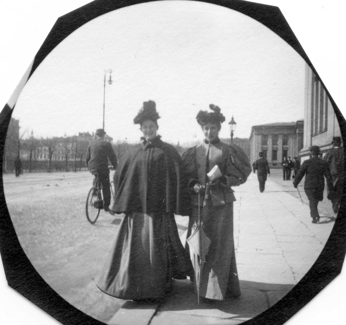 To damer spaserer langs Karl Johans gate, Oslo, på fortau utenfor Universitetet, Oslo. Syklist på vei i retning Slottet.