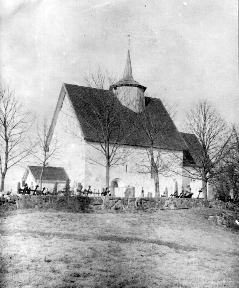 Eksteriørfoto av Bø gamle kirke med kirkegård og gravstøtter.