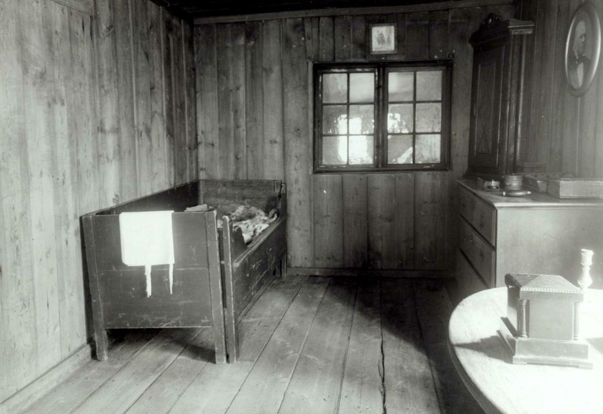 Vesterhaug, Elverum, Sør-Østerdal, Hedmark. Interiør fra kammers med seng, komode og bord. Nå på Glomdalsmuseet.