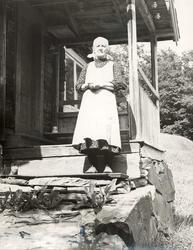 Portrett av Margit Kollberg, Lårdal, Tokke. Stående i trappa