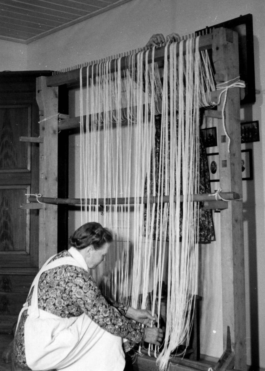 Veving på oppstadvev. Renningen ordnes. Tveita gård, Øvre Hålandsdal, Fusa, Hordaland 1956.
