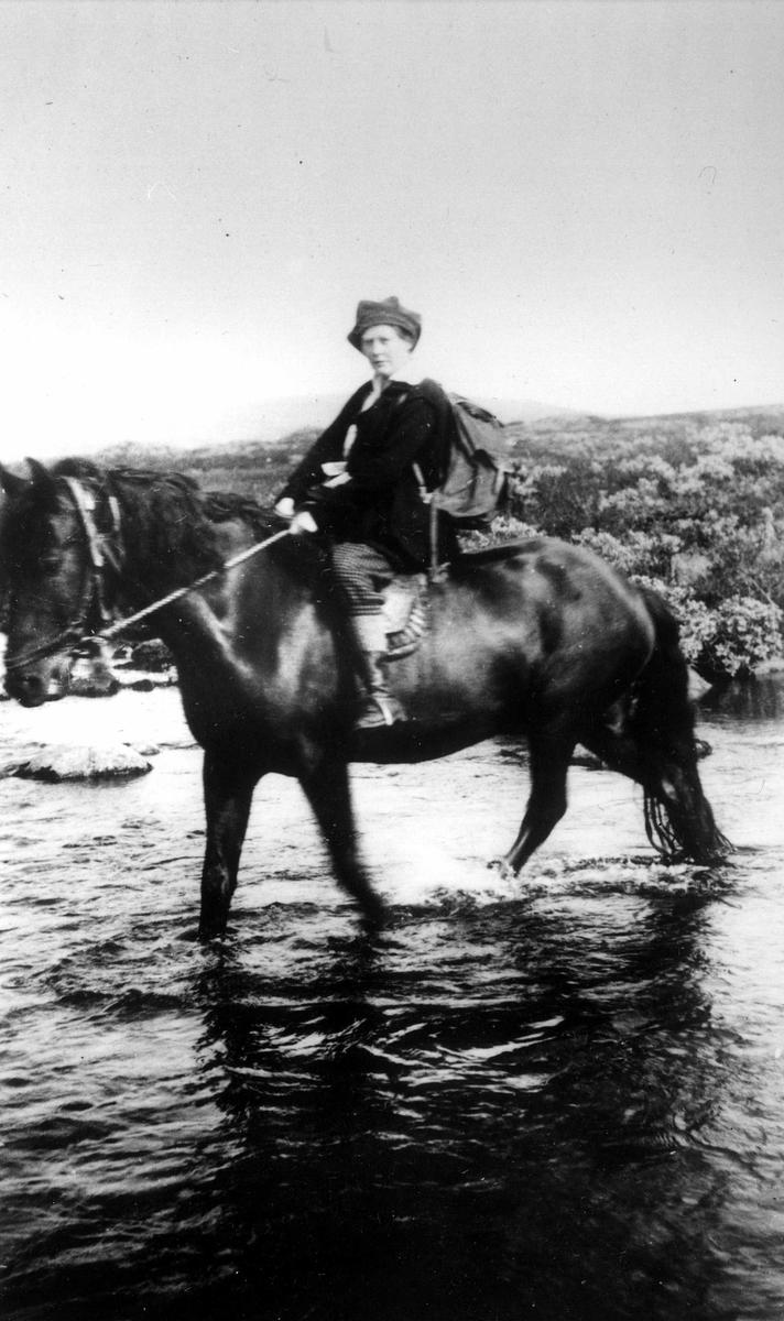 Kvinne på ridetur i fjellterreng. Familiemedlem krysser Øver-Åsta i Øyer  østfjell, Oppland med hest.  Fra Jorunn Fossbergs private fotoalbum.