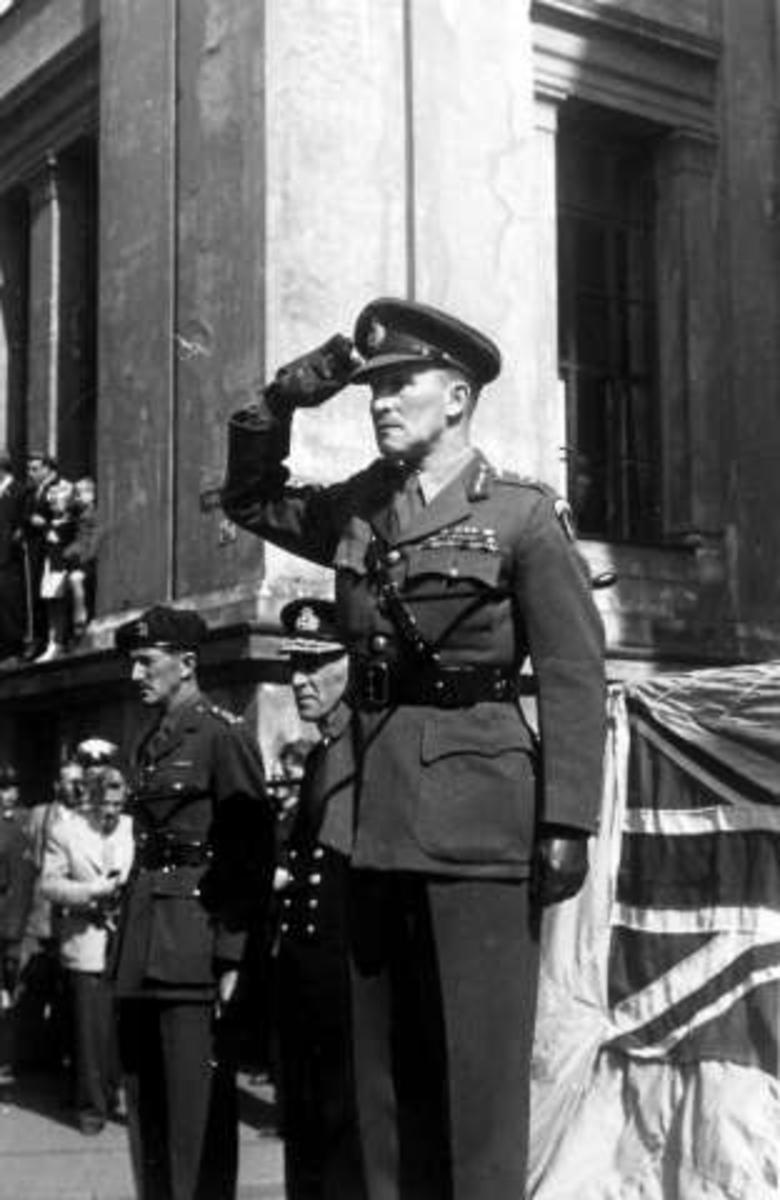 Fra fredsdagene i 1945.Uniformerte menn ved og på et platå, med det britiske flagg i bakgrunnen.Platået er plassert i krysset ved Universitetsgata og Karl Johans gate.